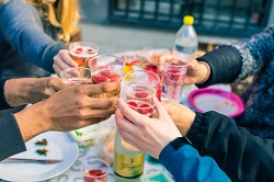 People enjoy drinking around a table outside