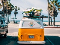 VW van with surf boards by beach