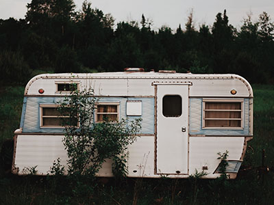 white RV trailer on grass field near trees under cloudy sky