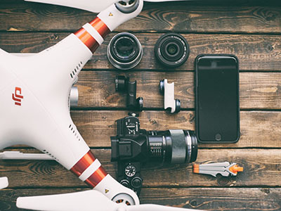 white and red DJI quadcopter drone, photographic camera and mobile phone