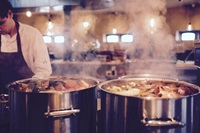 steaming cooking pots in restaurant kitchen