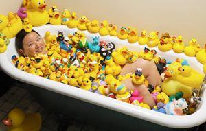 Charlotte Lee in bath of rubber ducks