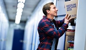 man putting boxes into storage locker