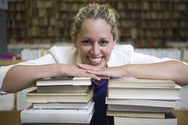 Woman entrepreneur leaning over pile of books