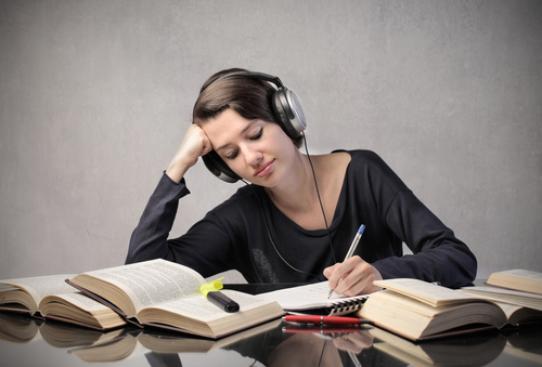student with headphones studying around a table full of books