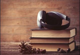 headphones resting on pile of books