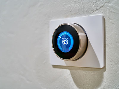 gray Nest thermostat displaying at 63