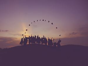 students silhouette on hill top