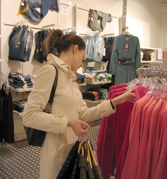 woman looking at clothes rail in shop
