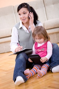 Mother on phone, baby girl looking at tablet