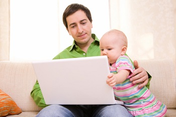 Father & baby looking at laptop screen.