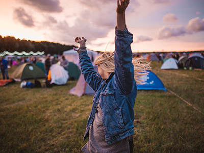 woman wearing multicolored shirt dancing in the middle of camping