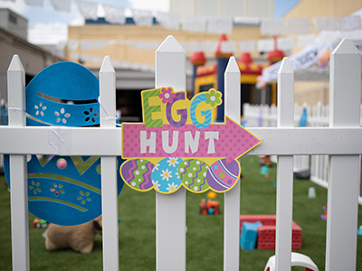 multicolored egg hunt decor on white wooden fence