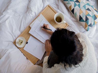 Girl in bed reading a working from home guide